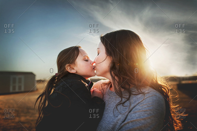 Mom giving a girl a kiss in front of a sunset