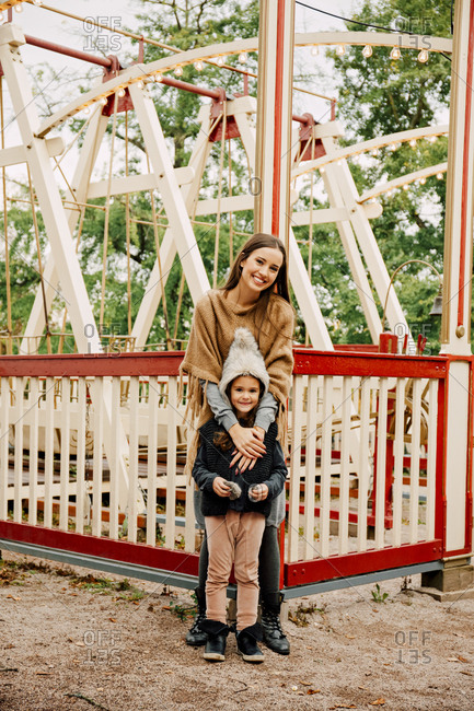Young woman and little girl standing in front of swing at fair