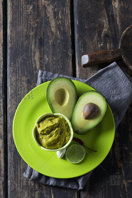 Bowl of Guacamole and ingredients on plate