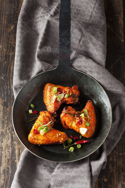 Three marinated and grilled chicken wings in cast-iron frying pan