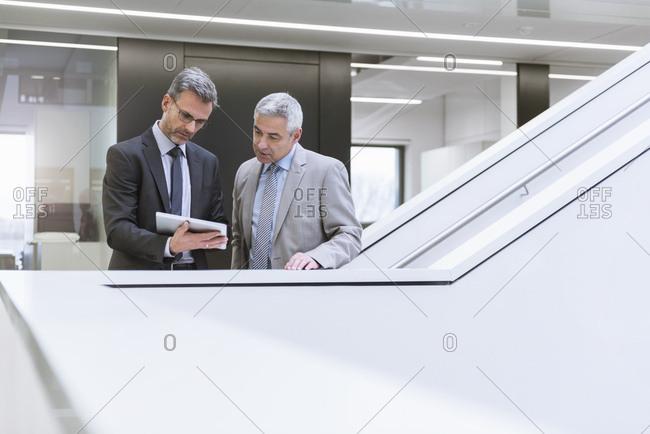 Two businessmen having an informal meeting - using digital tablet