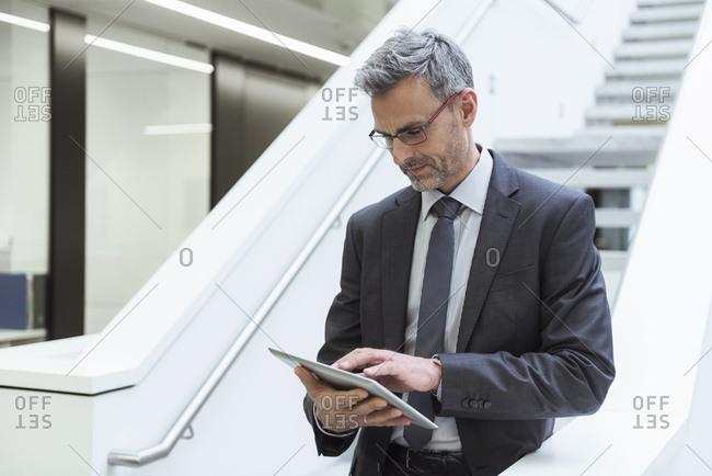 Portrait of a mature businessman - using digital tablet