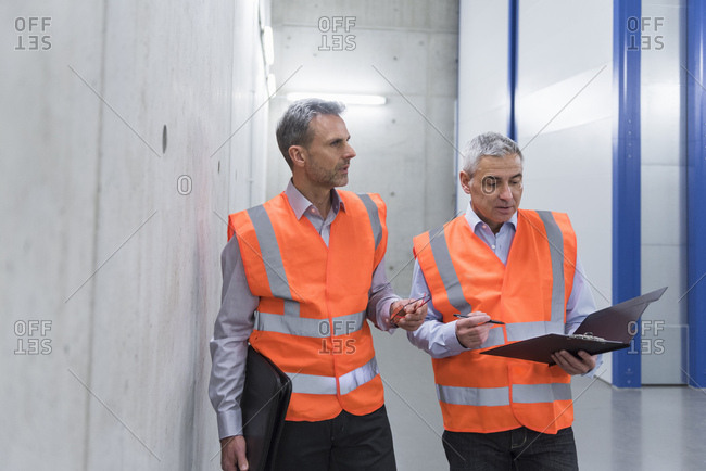 Two colleagues wearing safety vests holding clipboard
