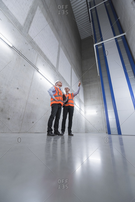 Two colleagues wearing safety vests and hard hats talking in a building