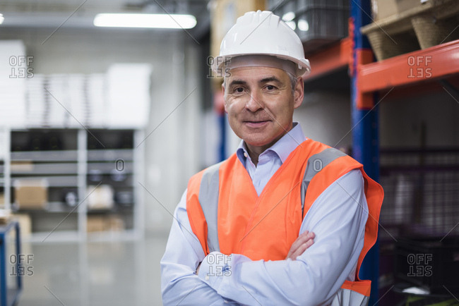Portrait of man in factory hall wearing safety vest and hard hat