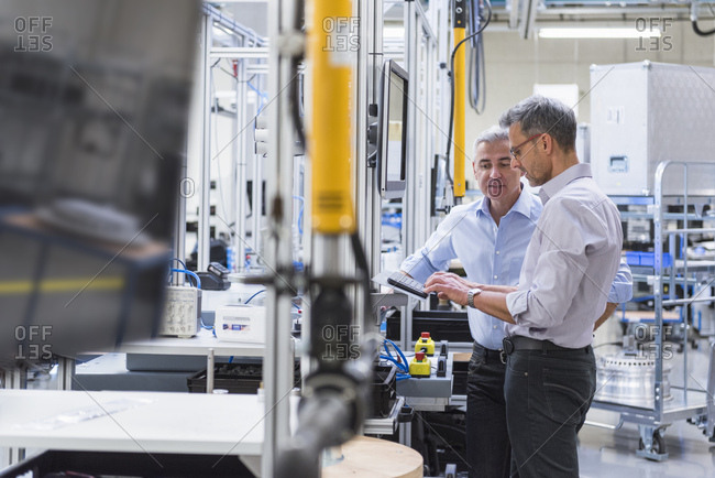 Two businessmen in modern factory hall using computer
