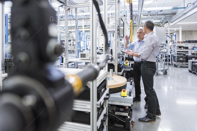 Two businessmen in modern factory hall talking