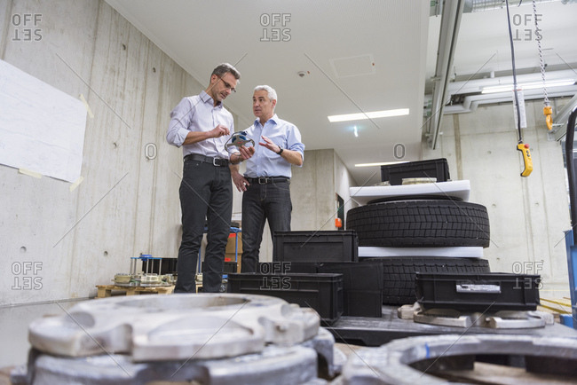 Two businessmen in factory hall with tires examining product