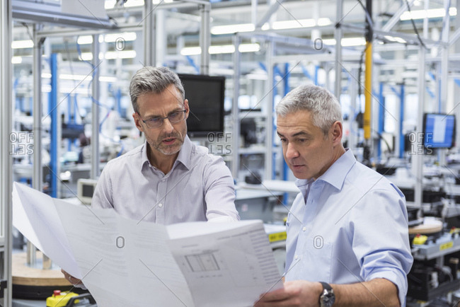 Two businessmen in factory hall discussing construction plan