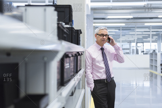 Manager on shop floor of a factory using smart phone