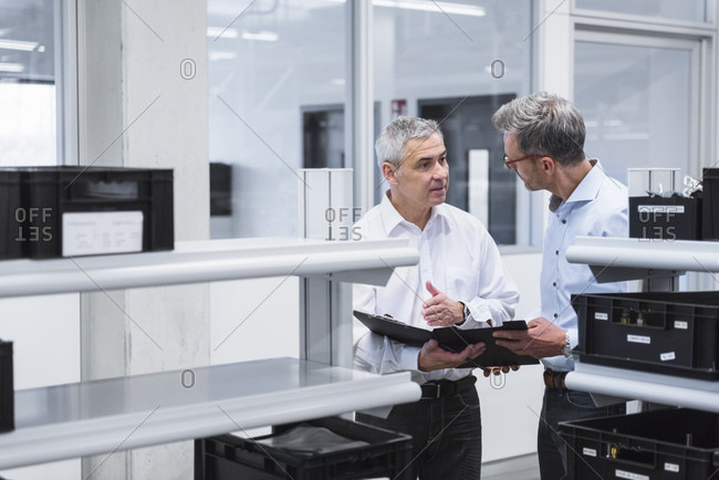 Two managers with files standing in comany - discussing
