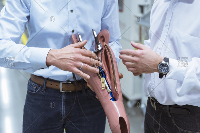Two managers discussing construction of an prosthetic leg