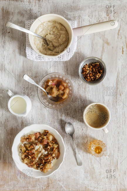 Breakfast with bowl of porridge with rhubarb compote - honey and nuts and cup of coffee