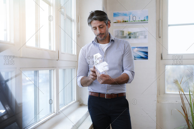 Man in office looking at architectural model