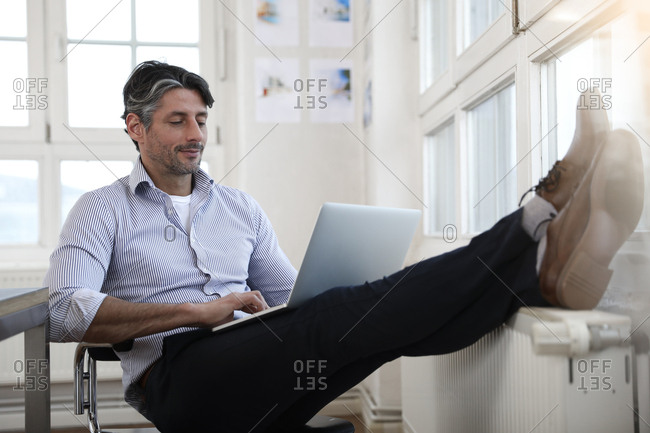 Man using laptop at the window in office