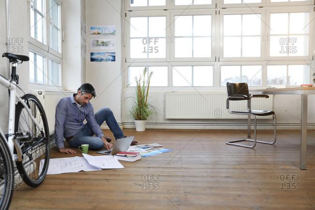 Man using laptop on the floor in a modern informal office