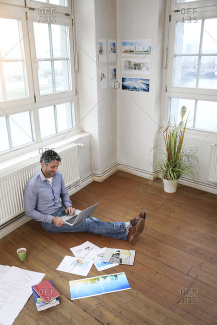 Man using laptop on the floor in office