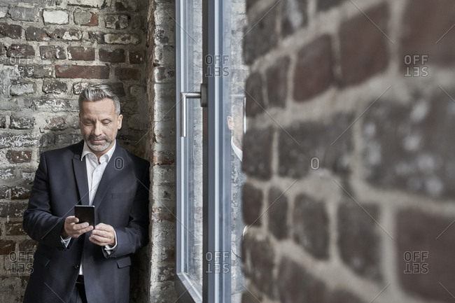 Businessman at a brick wall checking cell phone