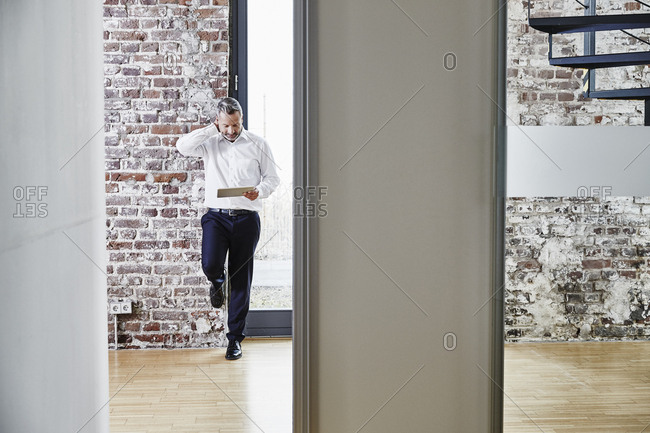 Businessman looking at tablet on modern office floor