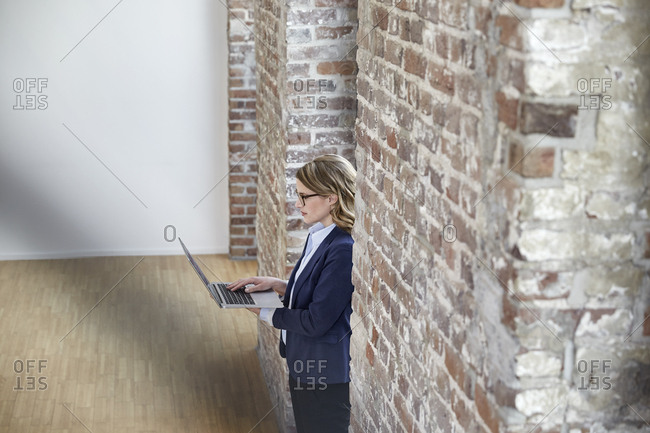 Businesswoman on modern office floor using laptop