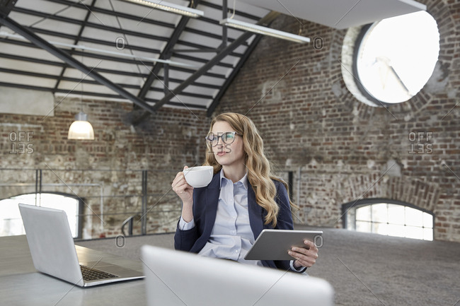 Businesswoman with cup of coffee and tablet at table in a loft
