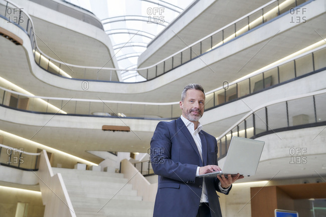 Businessman using laptop in modern office building