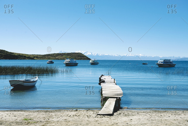 Bolivia - Titicaca lake - Isla del sol - pier and boats with the Andes in the background