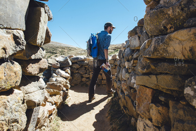 Bolivia - Titicaca lake - Isla del sol - man with backpack and guidebook walking among the Chinkana ruins