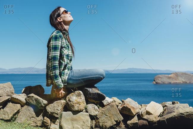 Bolivia - Titicaca lake - Isla del sol - woman sitting on an old stone wall