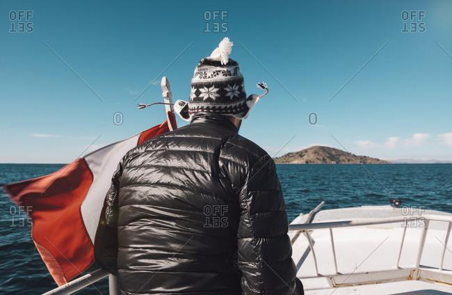 Peru - Titicaca lake - Taquile - man on a boat with Peruvian flag