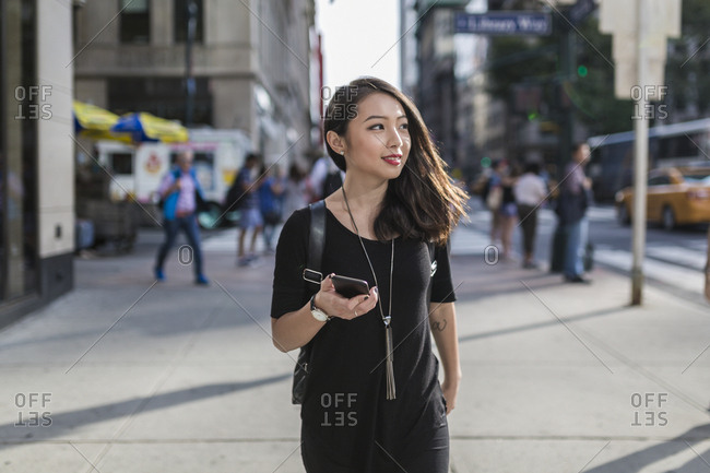 USA - New York City - Manhattan - portrait of young woman with cell phone dressed in black