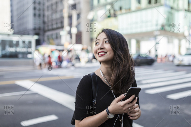 USA - New York City - Manhattan - young woman listening music with cell phone and earphones on the street
