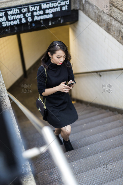 USA - New York City - Manhattan - young woman dressed in black walking upstairs looking at cell phone