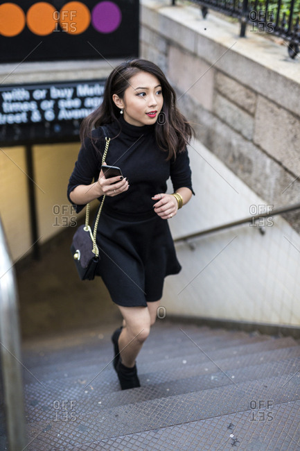 USA - New York City - Manhattan - young woman dressed in black walking upstairs