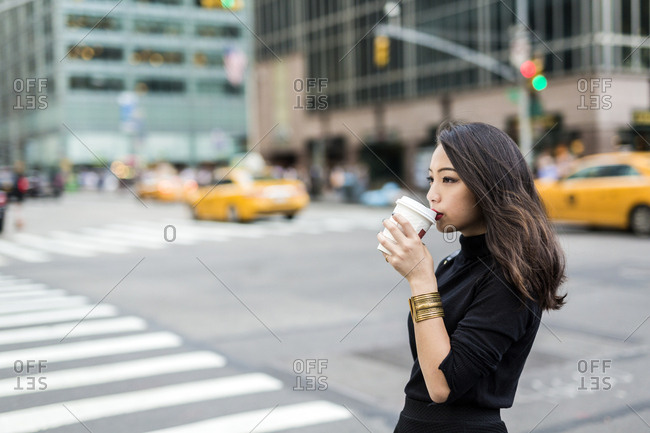 USA - New York City - Manhattan - young woman drinking coffee to go on the street