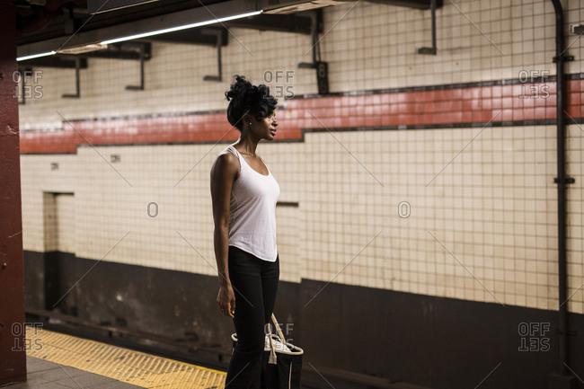 USA - New York City - Manhattan - woman with shopping bag waiting at subway station platform