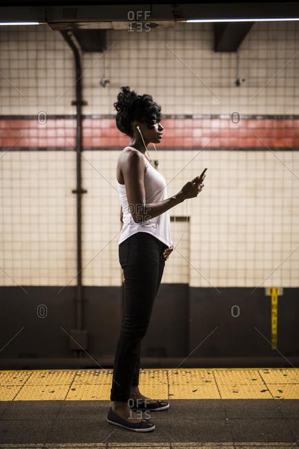 USA - New York City - Manhattan - woman waiting at subway station platform