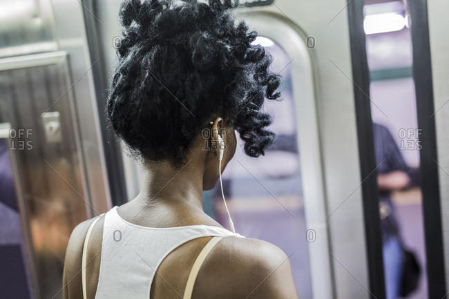 Back view of woman with earphones in underground train