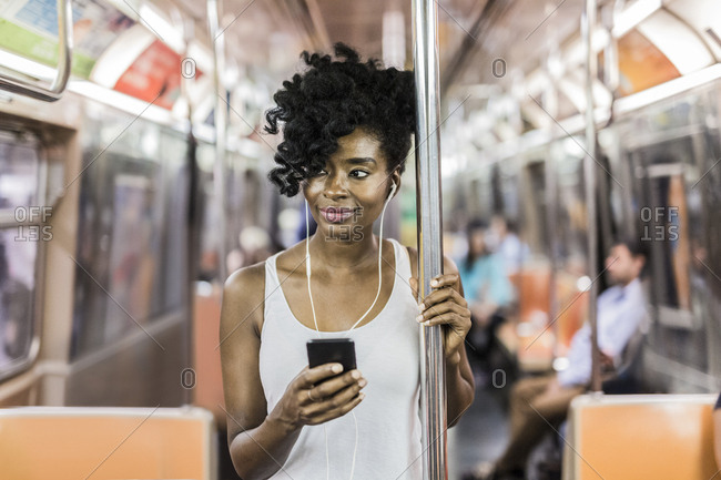 USA - New York City - Manhattan - portrait of relaxed woman with cell phone in underground train
