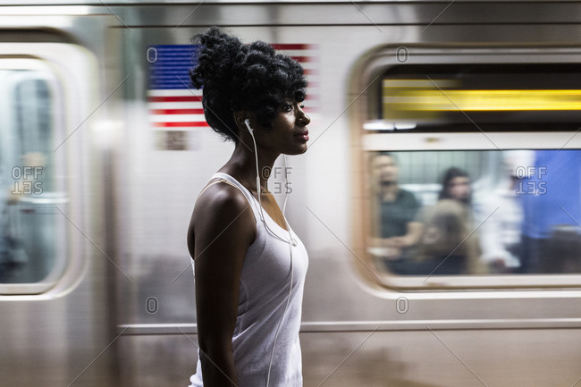 USA - New York City - Manhattan - woman with earphones on subway station platform