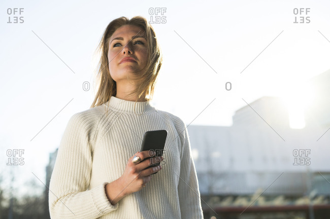 Portrait of young woman with cell phone looking at distance