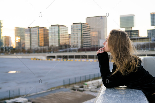 Spain - Barcelona - pensive young woman leaning on wall looking at distance