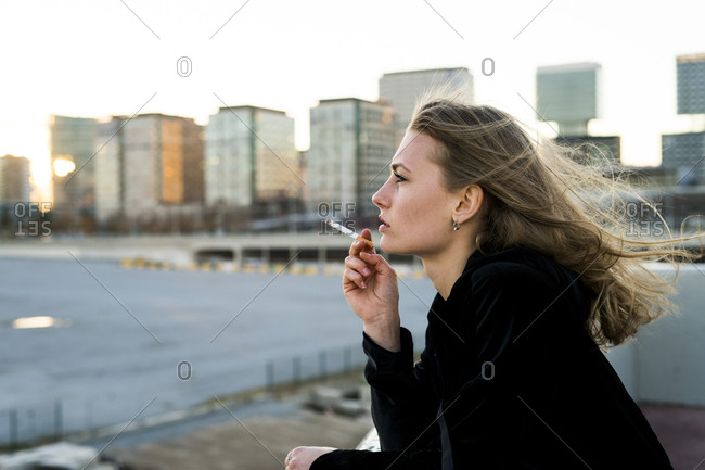 Spain - Barcelona - pensive young woman smoking cigarette