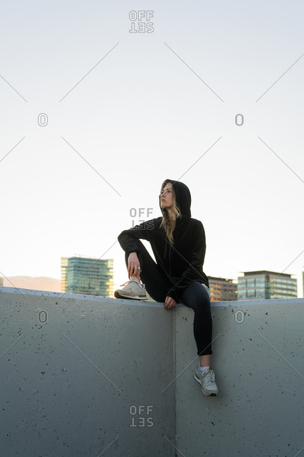 Spain - young woman dressed in black sitting on a wall looking at distance