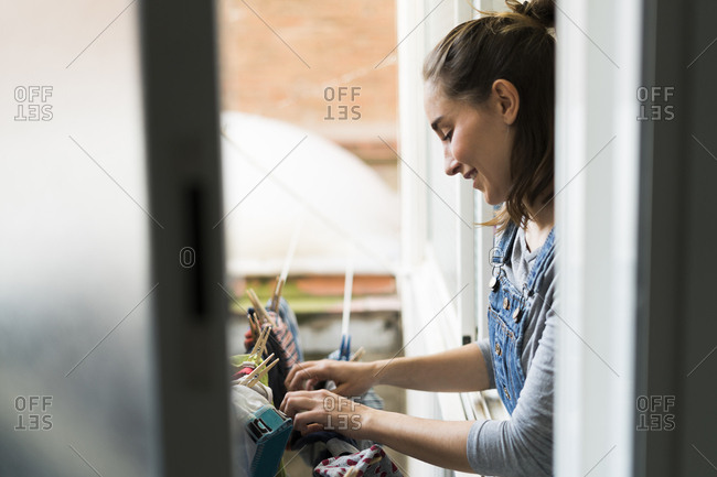 Young woman hanging up laundry on balcony