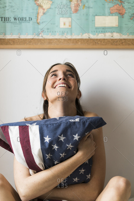 Smiling young woman holding US cushion under world map