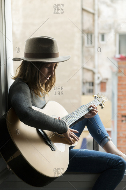 Young woman sitting in window frame playing guitar