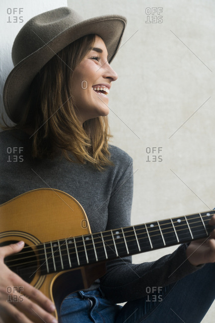 Happy young woman playing guitar
