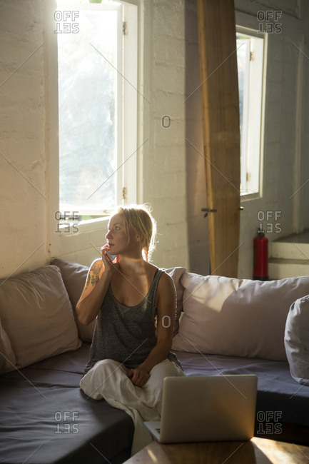 Blond woman on the phone sitting on the couch