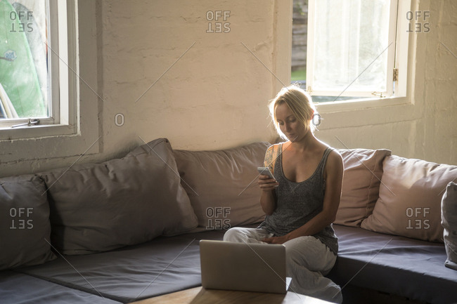 Blond woman sitting on the couch looking at cell phone